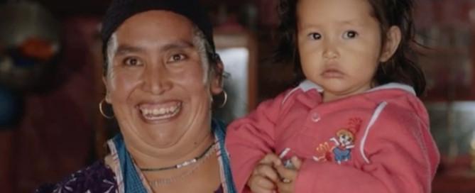 NRECA International Program: mother holding daughter smiling as lights come on